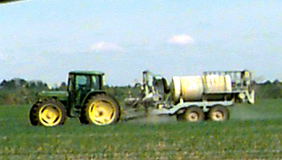 Photo of a tractor pulling an air assisted sprayer across a field of crops