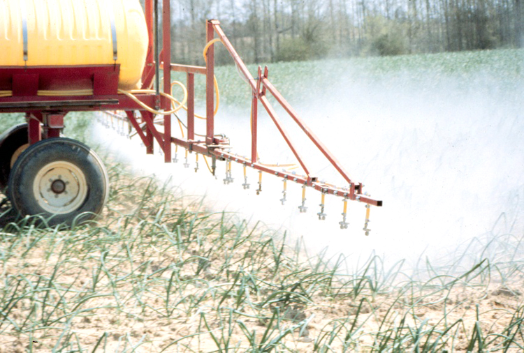 Photo showing a boom sprayer applying chemicals to crops