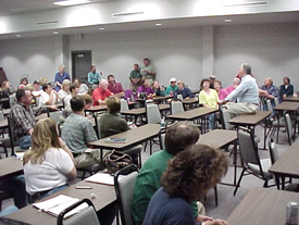 The composition is changed from one that lacks interest to a dynamic one by taking thepicture from a different vantage point in the room. Not only does it show more people attending this meeting, but it shows the speaker engaged in conversation with the audience. The position of the speaker sitting among the audience members (right) compared to standing in front of them conveys the impression of an earnest two-way discussion and infinitely more dynamics.
