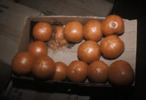 Photo showing box of soft and bruised tomatoes.
