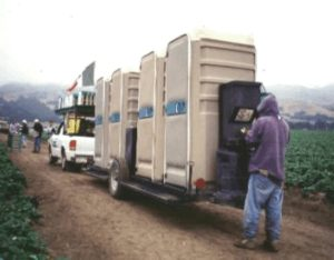 Photo showing portable toilet units with a worker using a handwashing station in a field