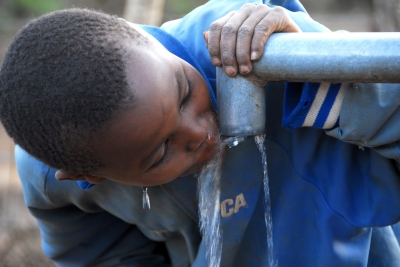 Photo of a child drinking water from an outdoor spigot