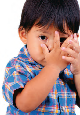 boy covering face with hands (stock photo)