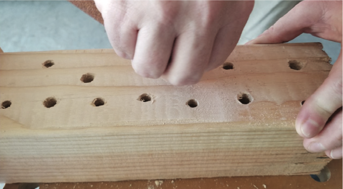 A piece of wood with holes drilled into it