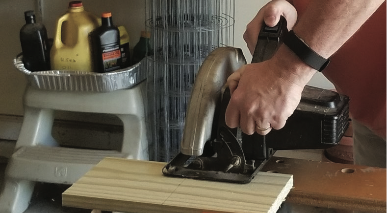 A person cutting a plank of wood