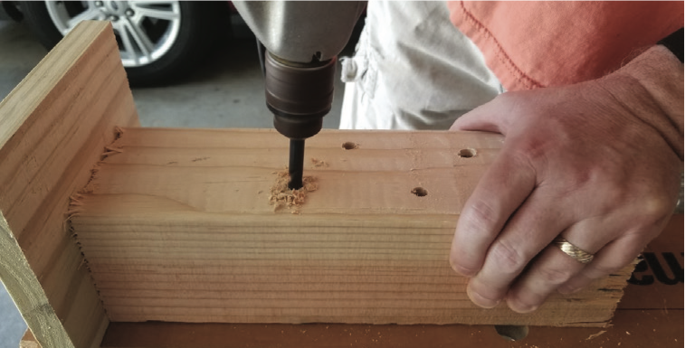 A person drilling into wood