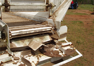 Side view of typical twin-disk spinner manure spreader truck.
