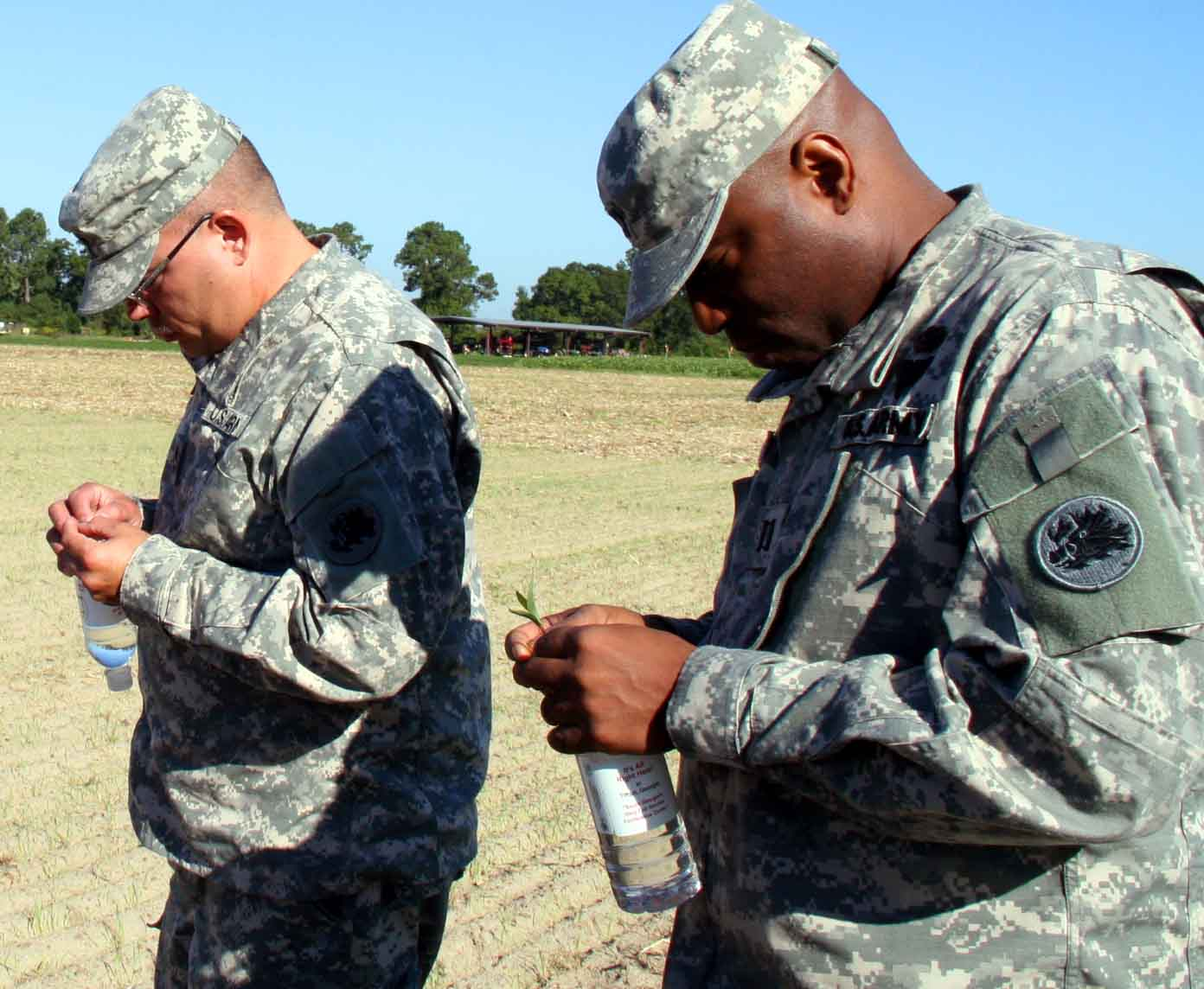 Two Georgia National Guardsmen examine wheat seedlings from a test field planted by UGA College of Agricultural and Environmental Sciences grain specialist Dewey Long. The guardsmen will deploy to Afghanistan in January.
