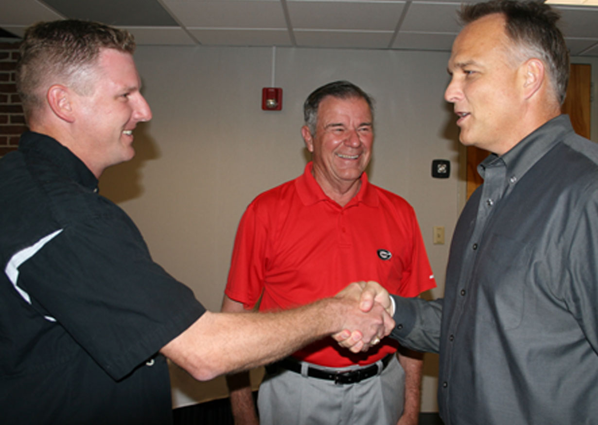 Georgia football coach Mark Richt, right, shakes hands with UGA College of Agricultural and Environmental Sciences Turfgrass breeder Brian Schwartz. Standing in the background is retired turfgrass breeder Wayne Hanna.