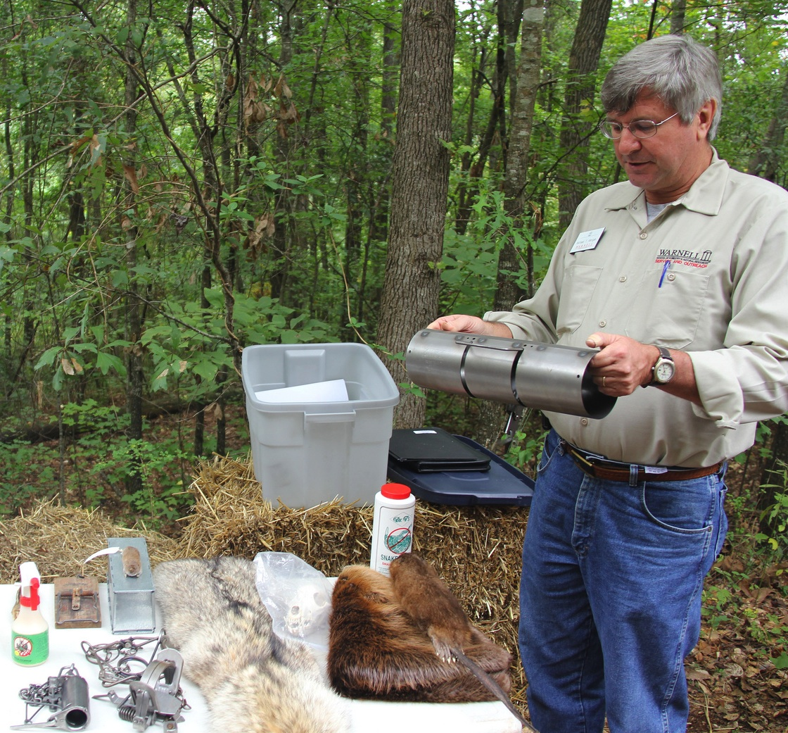 University of Georgia Cooperative Extension wildlife expert Michael Mengak tells visitors to a field day how a squirrel trap should be used.