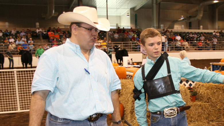 University of Georgia beef cattle specialist Jacob Segers talks with Dalton Whitley, an eighth grader from Piedmont Academy in Monticello, Ga., during a junior beef showmanship competition at the Georgia National Fair in Perry on Friday, Oct. 4.