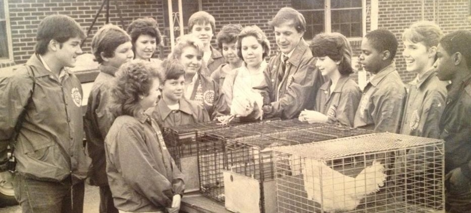 """Bo Ryles served as the 4-H agent in Clarke County (Athens). In this circa 1980's photo, he is shown teaching 4-H'ers what to look for when deciding which White Leghorn Hen had laid the most eggs. """"Every student had on a 4-H Jacket. That was a Clarke Co. 4-H tradition. When we put on the green, we were getting serious about competing,"""" Ryles said."""