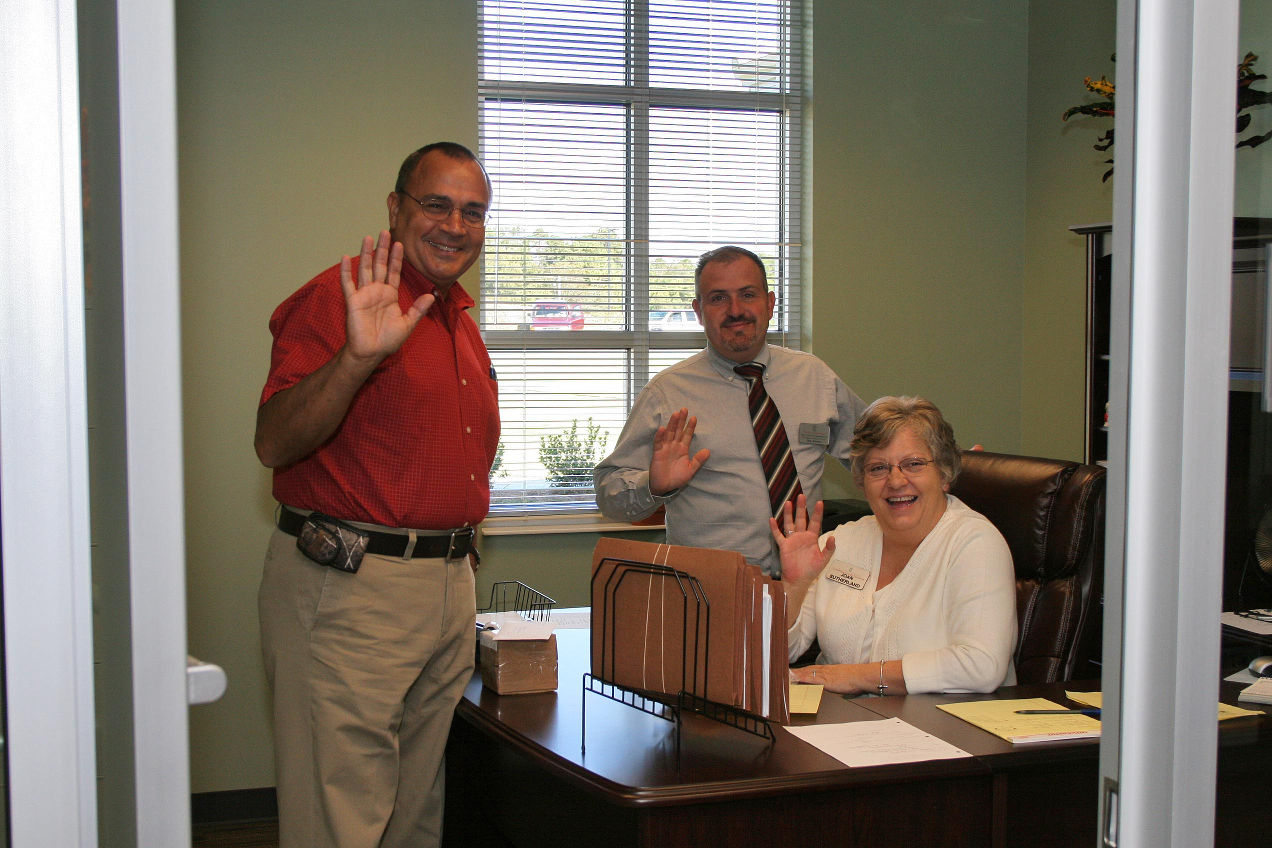 Former Gordon County Extension Agent Steve Moraitakis, current Gorden County Extension Coordinator Greg Bowman and Joan Sutherland, Gordon County Extension Secretary wave hello from their new headquarters at the Gordon County Ag Service Center.