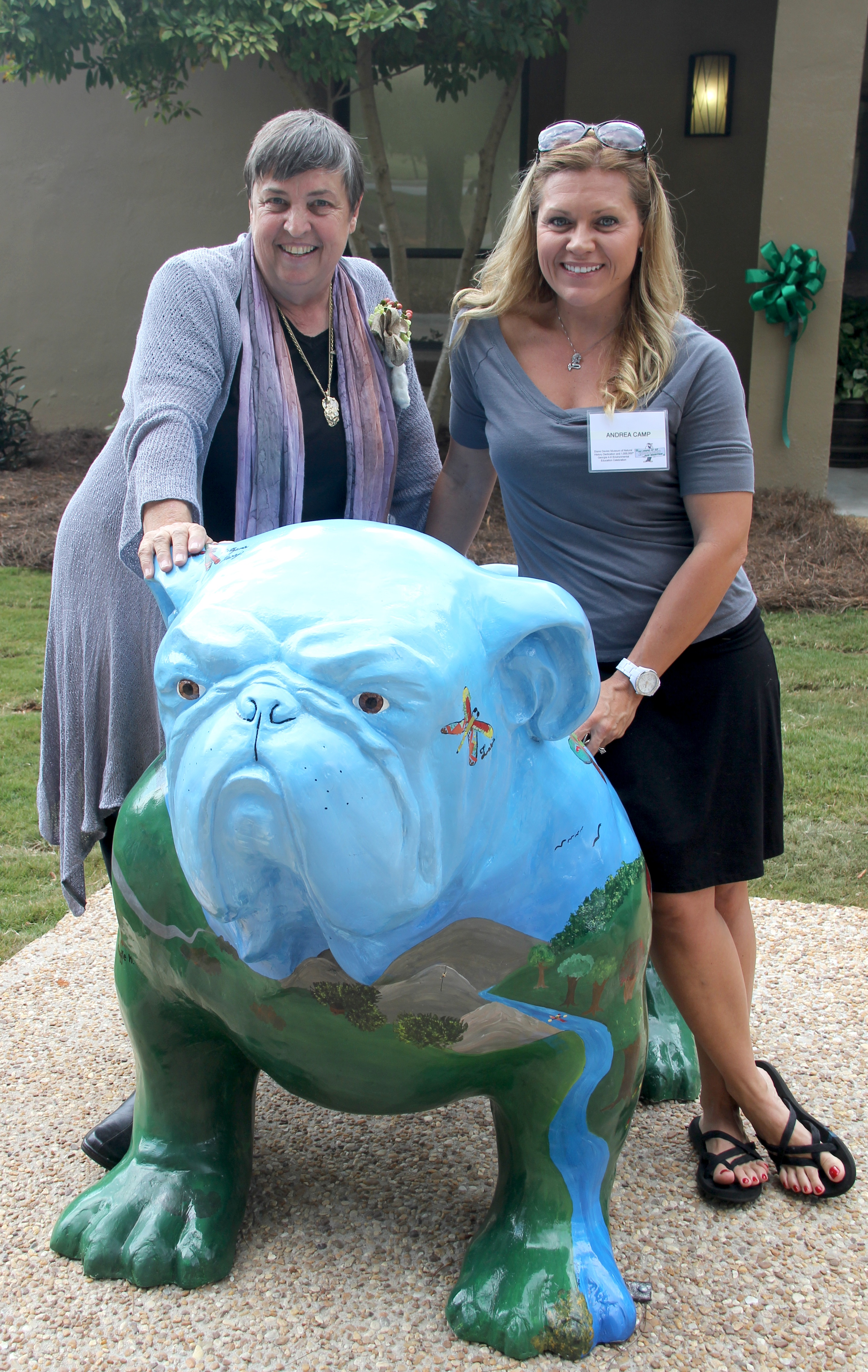 Diane Davies and Andrea Camp pose with the new University of Georgia Dawg, Tera, in front of the Diane Davies Natural History Museum at Rock Eagle 4-H Center in Eatonton, Ga. Davies founded the Georgia 4-H Environmental Education Program which began at Rock Eagle. Camp, a former environmental education instructor at Rock Eagle, painted Tera's artwork.