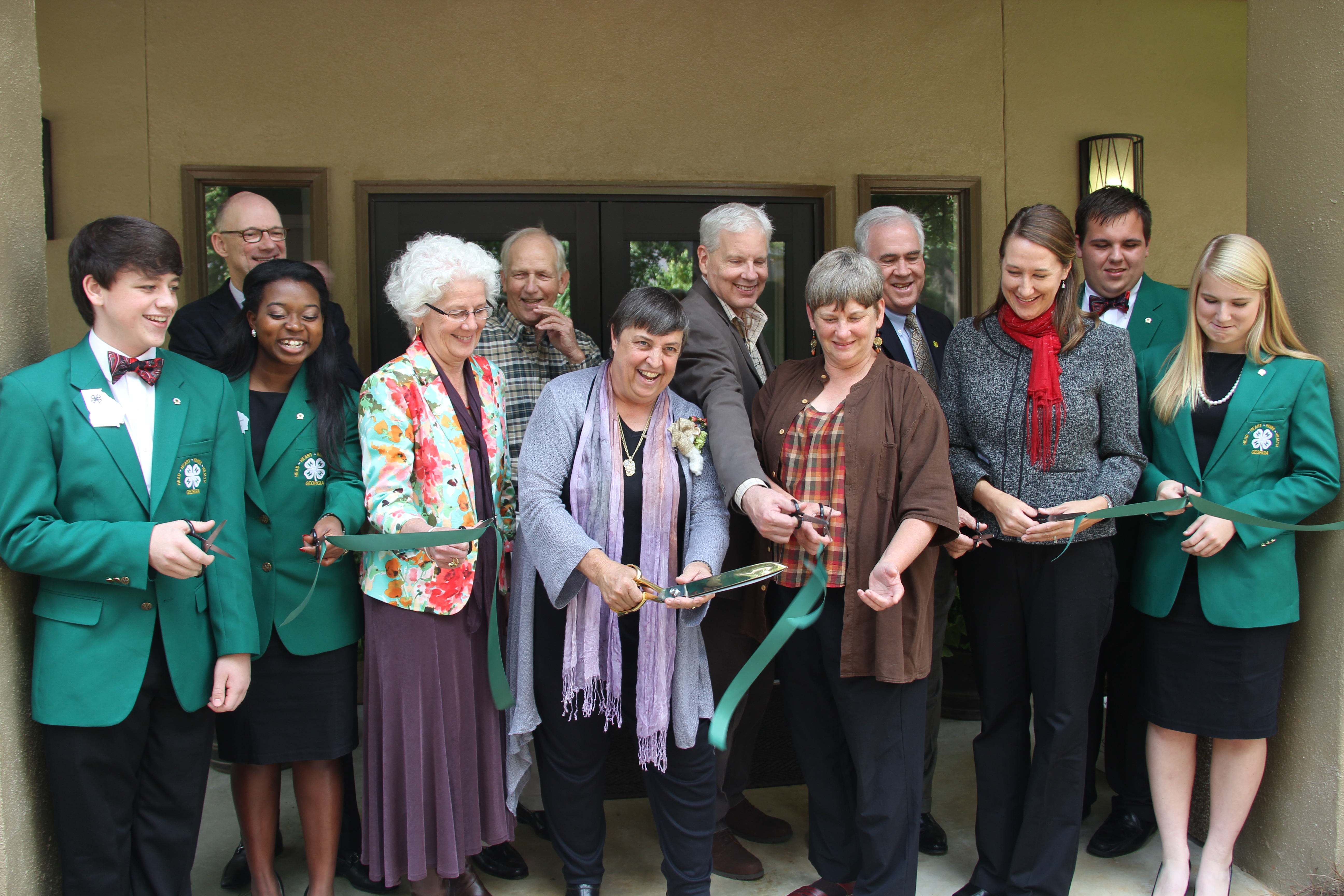 Diane Davies wields a ceremonial pair of scissors to cut the ribbon at Rock Eagle 4-H Center museum that now bears her name. The Diane Davies Natural History Museum honors Davies for creating the Georgia 4-H Environmental Education Program. Pictured left to right during the ribbon cutting are Georgia 4-H State Representative Brett Allen, Georgia 4-H State Represenative Maya Mapp, University of Georgia Cooperative Extension Associate Dean Beverly Sparks, Davies, Sara Thompson, Georgia 4-H Environmental Education Program Director Melanie Biersmith, Georgia 4-H Northeast District Representative Elizabeth Savage, (back row) Georgia 4-H Foundation Board of Trustees Chairman Jay Morgan, Retired Georgia 4-H State Leader Tom Rodgers, UGA College of Agricultural and Environmental Sciences Dean J. Scott Angle, Georgia 4-H State Leader Arch Smith and Georgia 4-H President Oakley Perry.