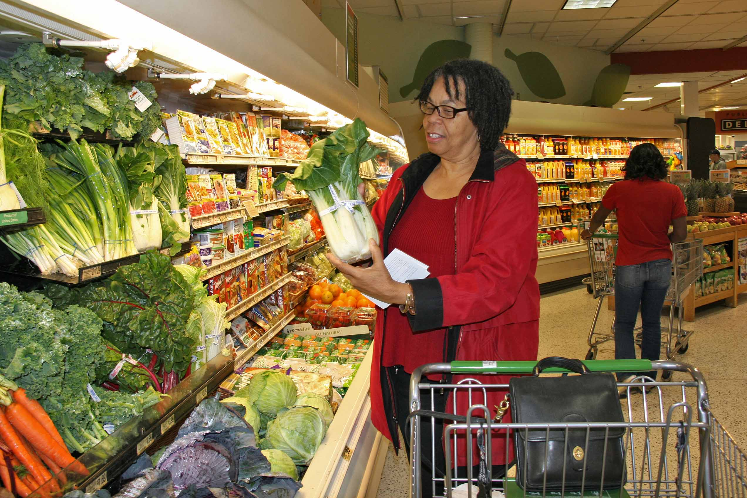 Sabrina Beasley, a UGA Extension Fulton Fresh participant, inspects a  bunch of  bok choy during a Fulton Fresh supermarket tour this winter.