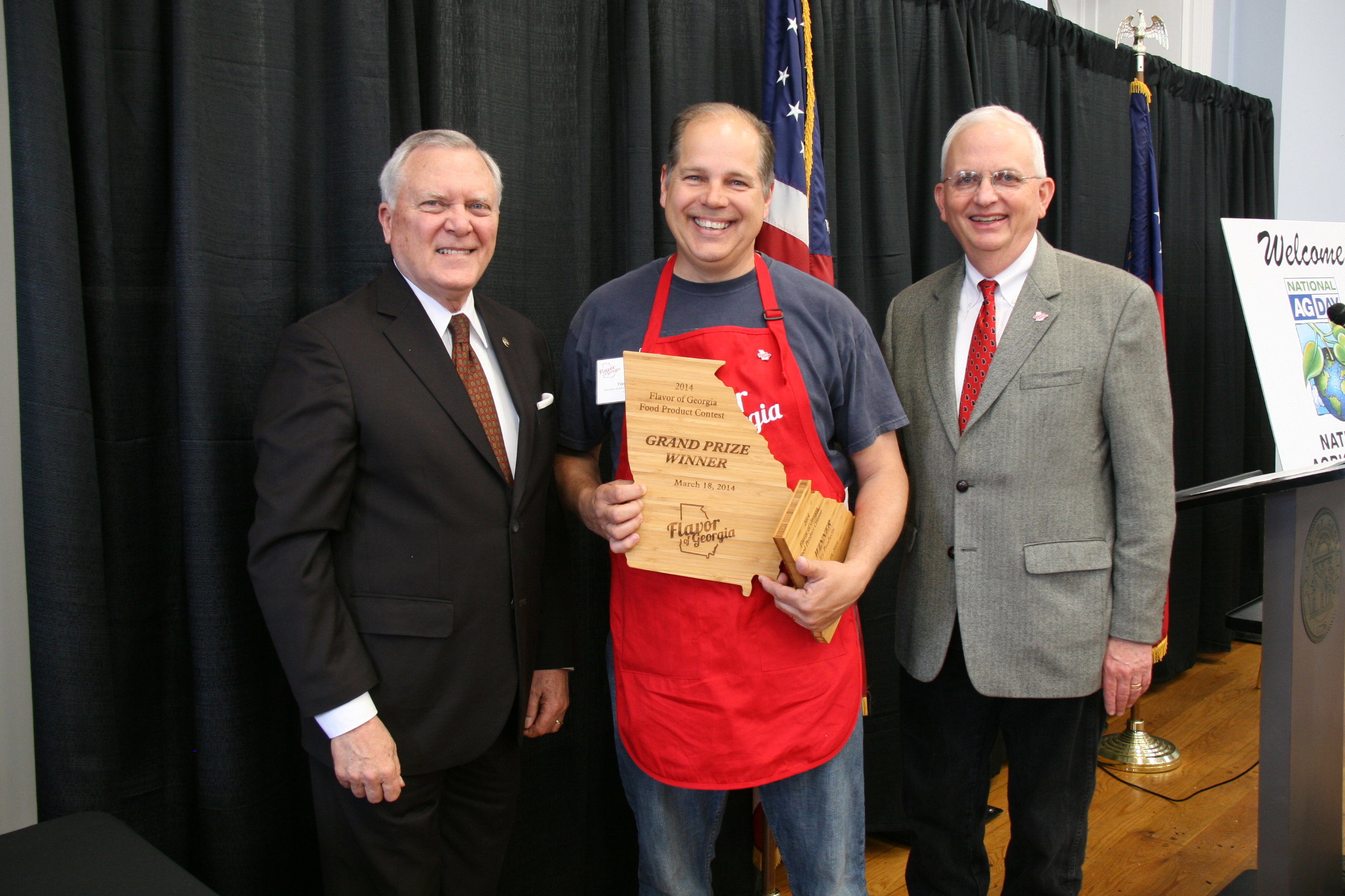 Tim Young, center, receives the Flavor of Georgia grand prize for his Georgia Gold Clothbound Cheddar from Gov. Nathan Deal and Agriculture Commissioner Gary Black after the 2014 contest.