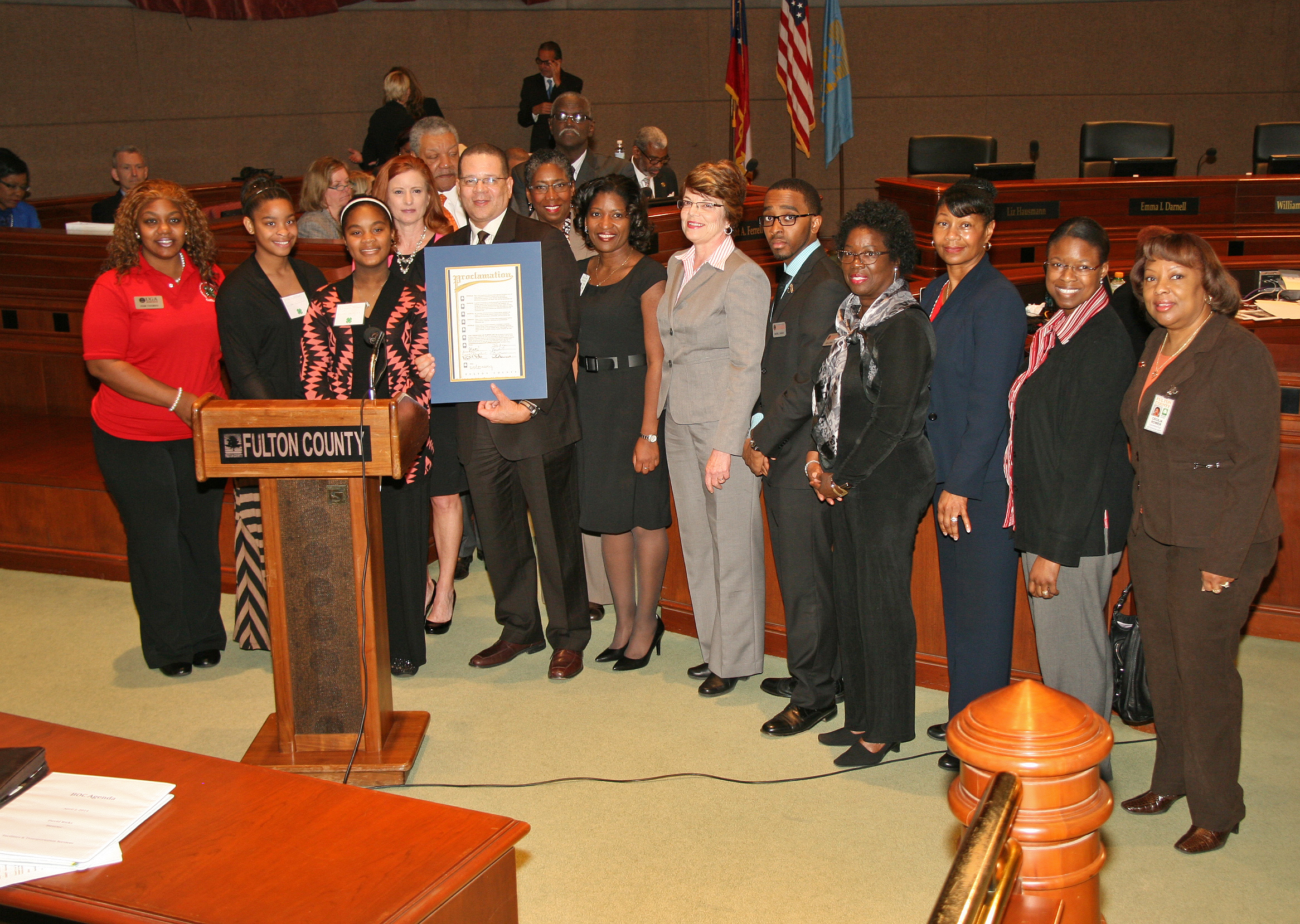 Fulton County Commission Chairman John Eaves presents a proclamation honoring UGA Extension's 100 years of service in Fulton County to County Extension Coordiantor Menia Chester, to his right; UGA Office of Environmental Sciences Director Susan Varlamoff, to her right, and the staff of the Fulton County UGA Extension Office.