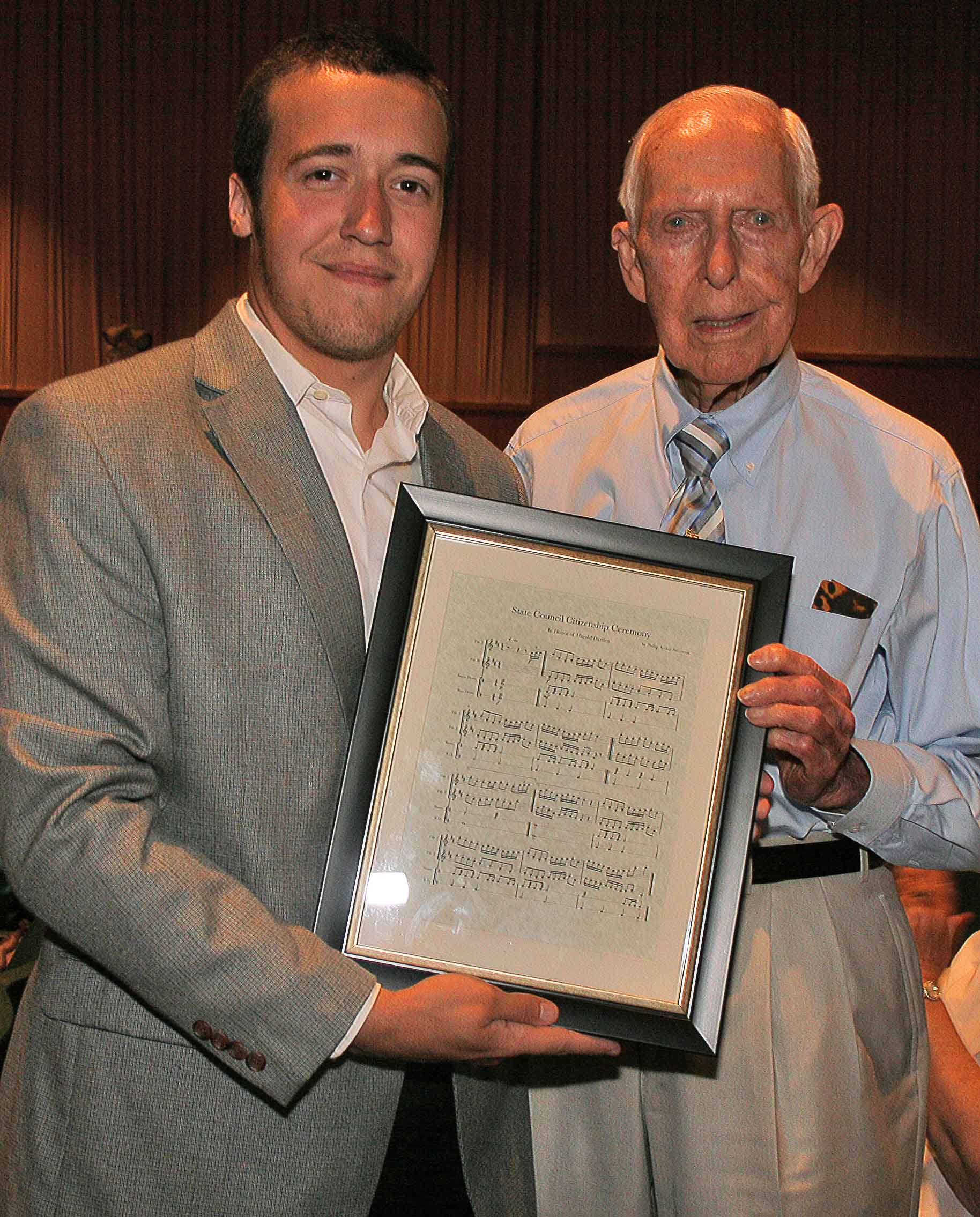 Former Spaulding County 4-H Club Member Phillip Simmons presents former Georgia 4-H State Leader Harald Darden with the sheet music that he wrote for the clubs State Council Citizenship Ceremony, which Darden created in 1959.