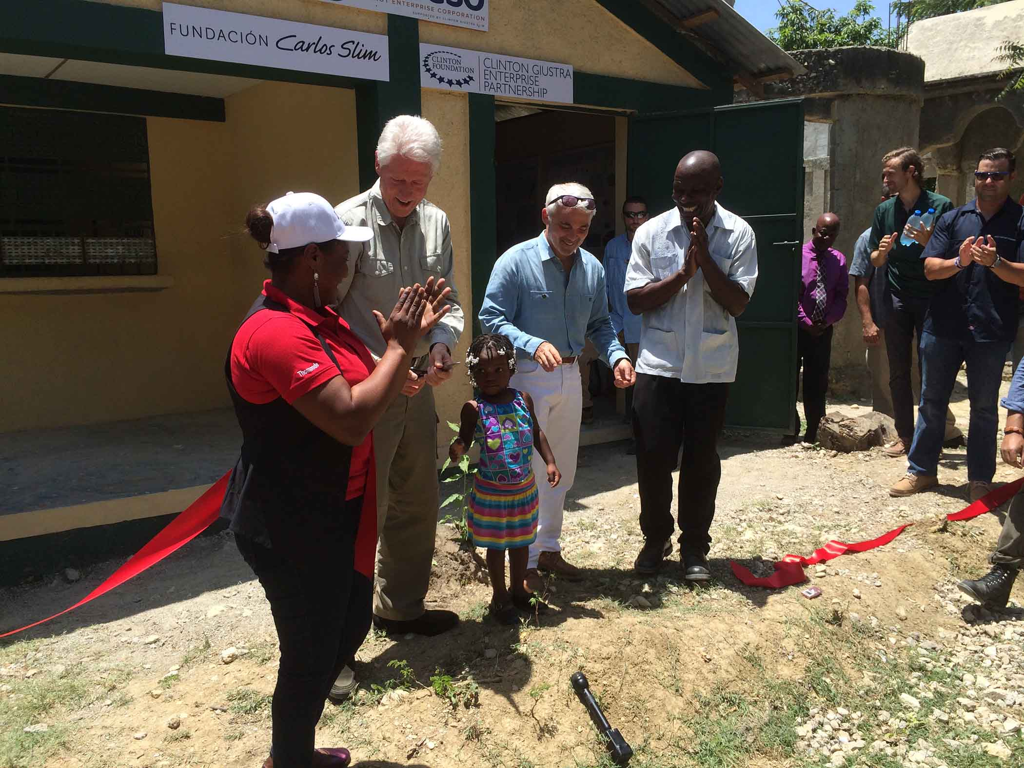 Former U.S. President Bill Clinton gathers with a group of townspeople from Tierra Muscady, Haiti, where he and philanthropist Frank Giustra launched the new Acceso Peanut Enterprise Corp., which is designed to improve the livelihoods of more than 12,000 smallholder peanut farmers.