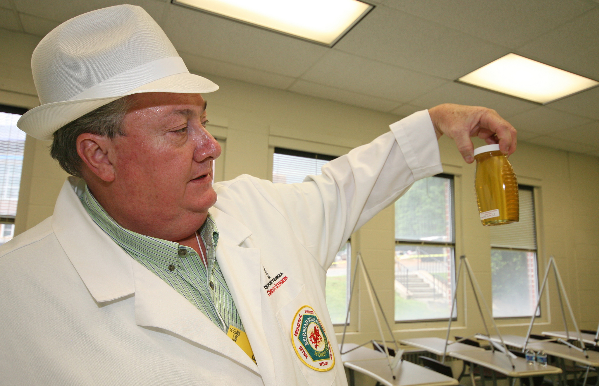 Putnam County Extension Coordinator Keith Fielder inspects a jar of honey. A Georgia Master Beekeeper, Fielder will lead a basic beekeeping class Aug. 7 in Madison.