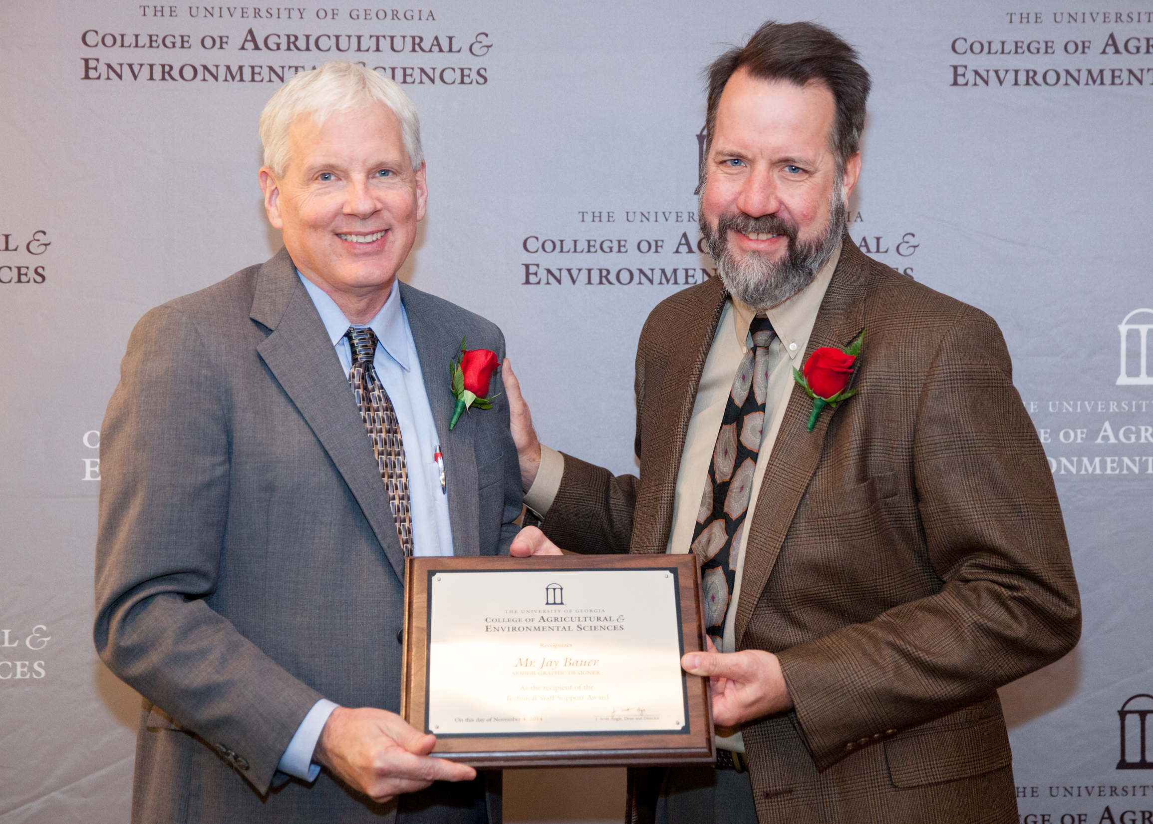Dean J. Scott Angle presents Jay Bauer, senior graphics designer in the Office of Communication and Creative Services, with the CAES Staff Award for Technical Support. Bauer created the college's mascot, Caesar, when he started at the college 13 years ago. Most recently, he created a museum exhibit to celebrate the centennial of the UGA Extension.