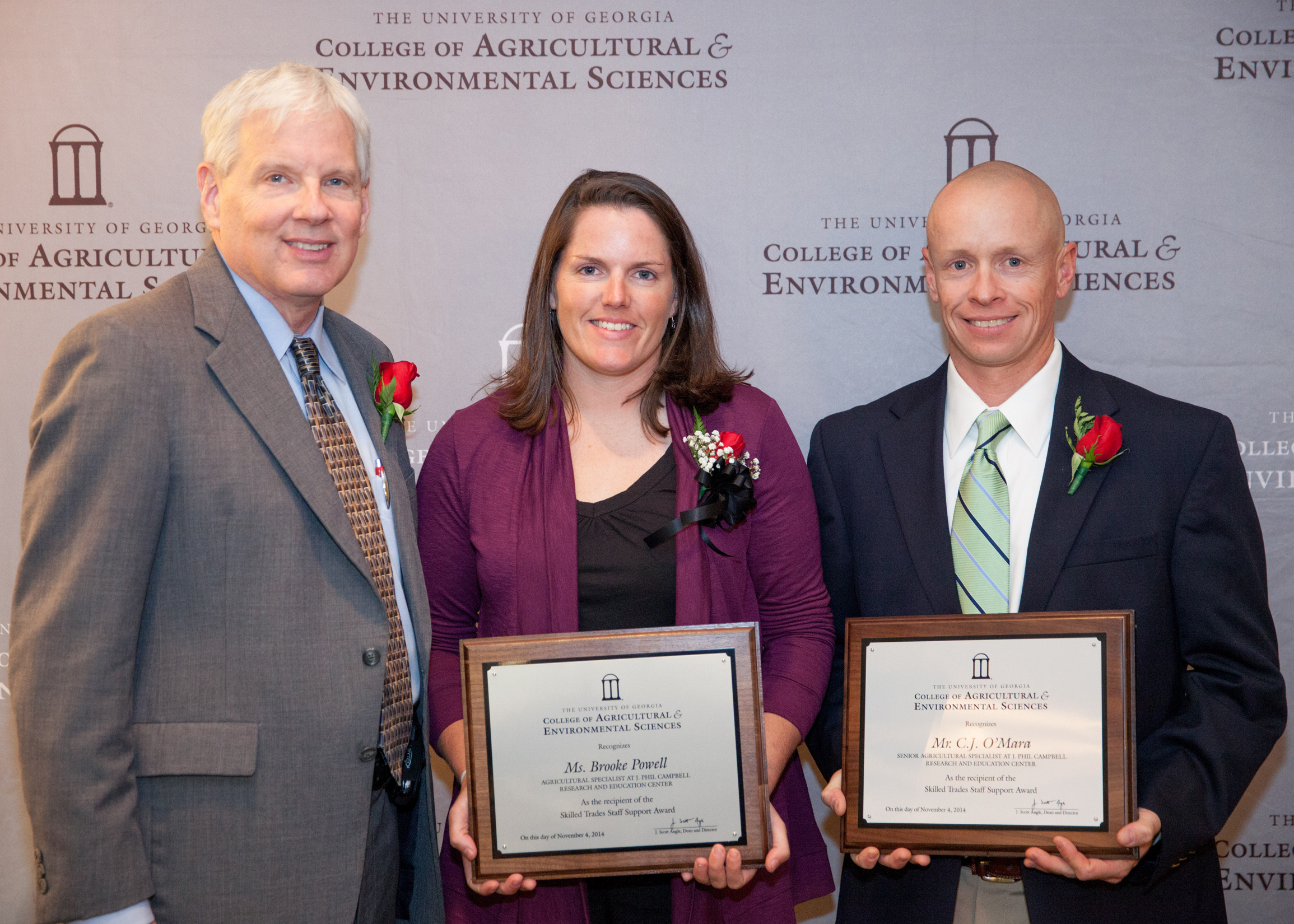 Dean J. Scott Angle presents C.J. O'Mara, senior agricultural specialist, and Brooke Powell, agricultural specialist, of the J. Phil Campbell Sr. Research and Education Center, with the CAES Award for Skilled Trades Support. O'Mara and Powell managed the on-the-ground transition of the 1,055-acre research farm as is it changed hands from the U.S. Department of Agriculture to UGA's ownership.
