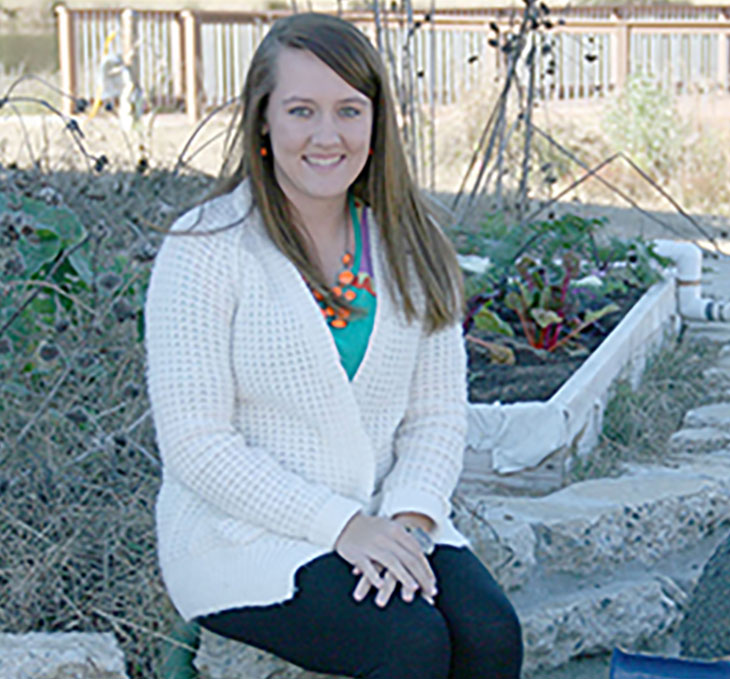 Amanda Miller sits next to her aquaponics system located behind the Future Farmstead on the UGA Tifton Campus.