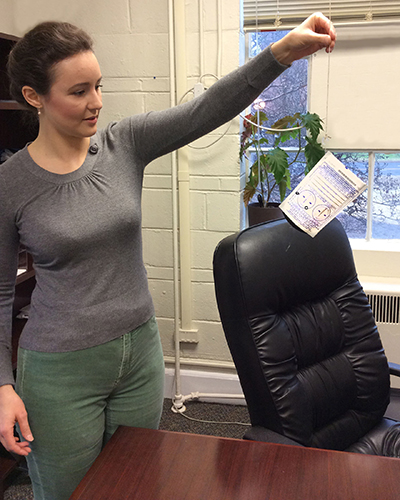Kathryn Holland, a graduate student in the College of Family and Consumer Sciences, prepares to hang a radon testing kit in her office.