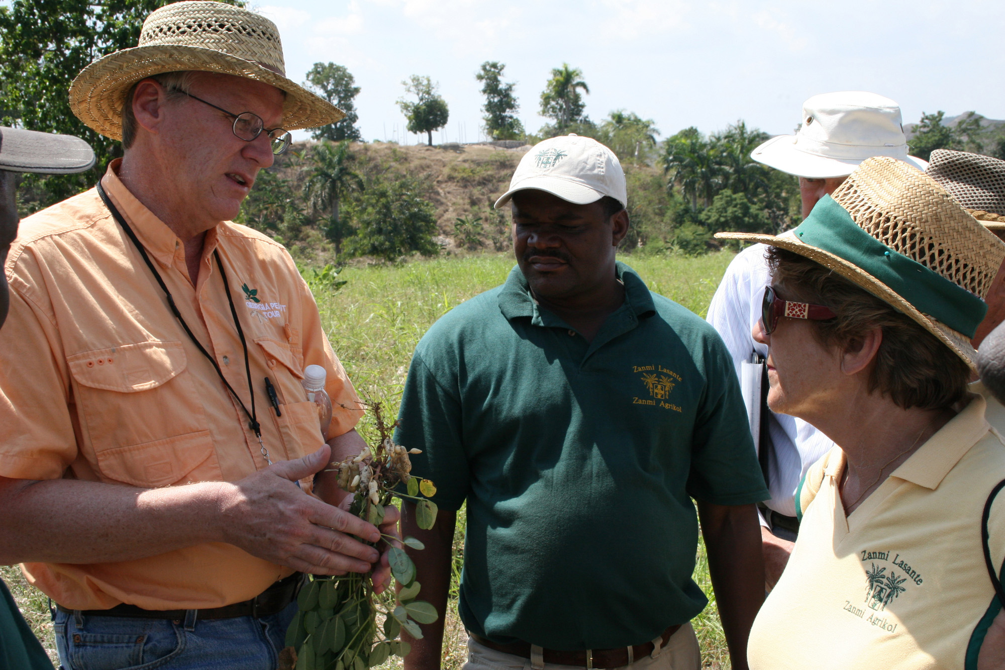 UGA Cooperative Extension assistant dean Steve Brown (left) explains peanut diseases to Zanmi Agrikol agronomist Fereste Sonnius (center) and director Gillaine Warne (right) at one of the organization's farms March 17.