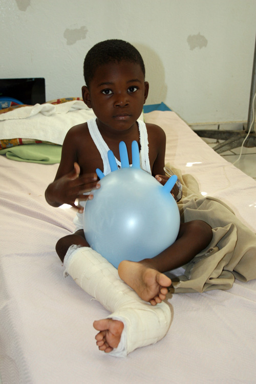 Haitian boy plays with a surgical-glove balloon March 18 inside Zanmi Lasante Sociomedical Complex, a sprawling medical facility and school founded in Cange, Haiti, by Boston-based Partners in Health.