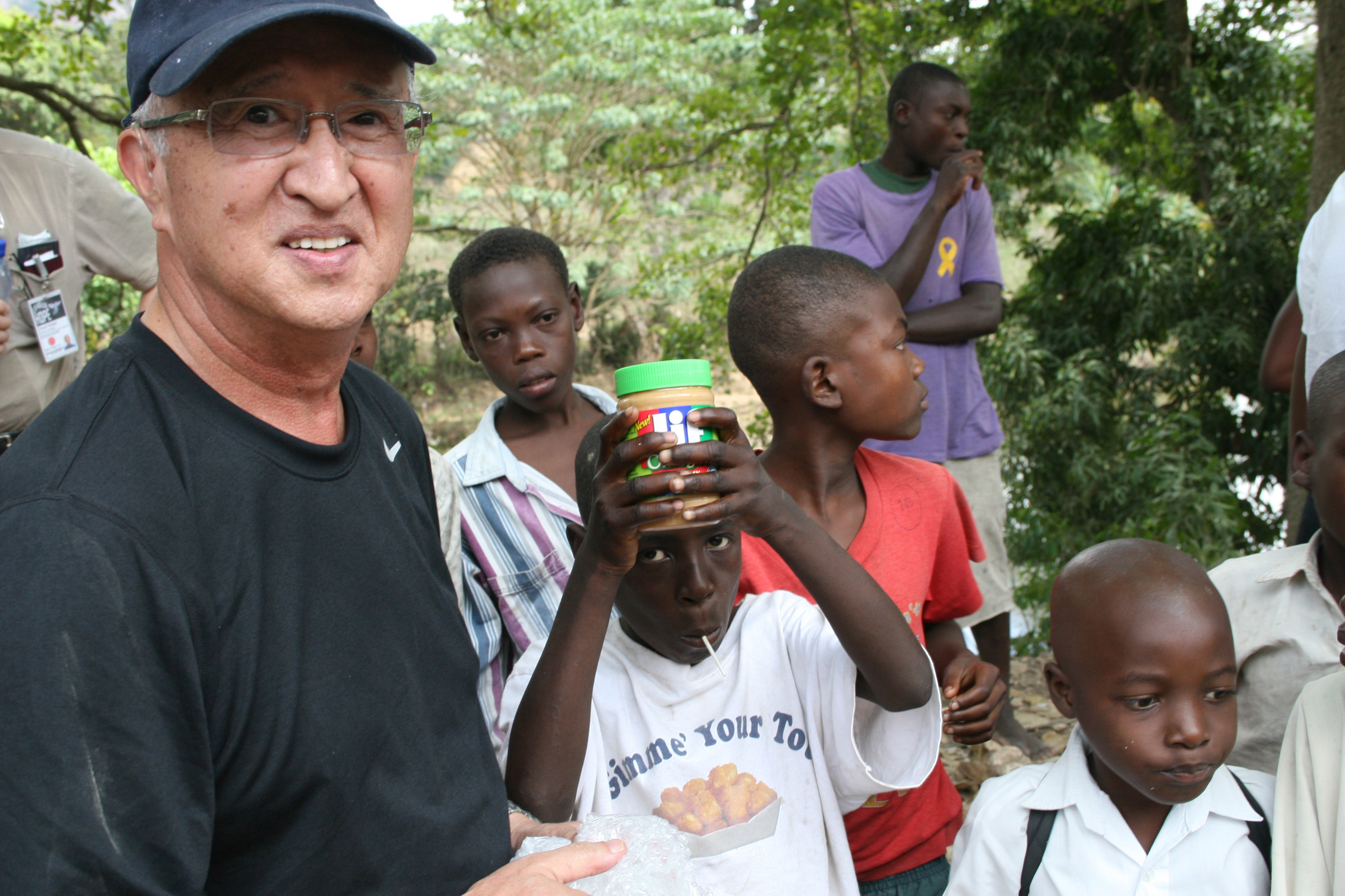 Ed Kanemasu, CAES director of global programs, distributes peanut butter to children on the road from Cange to Terrier Rouge, Haiti, March 18.