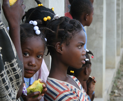 Children eat mangoes and stare at UGA agricultural experts working in a field near Los Palis, Haiti, March 16.