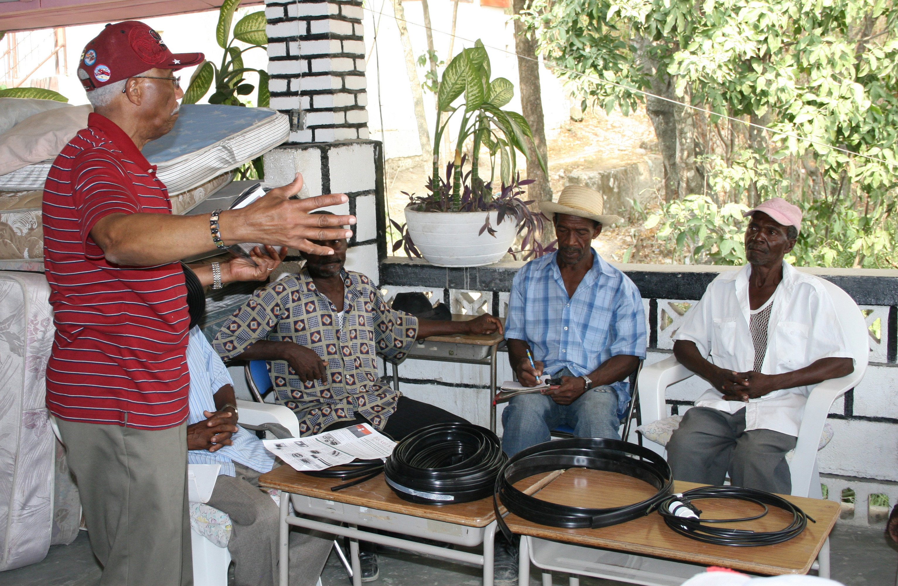 Suchet Loois (left) teaches drip irrigation techniques to Haitian farmers March 16. The Haitian native and retired Tuskegee University professor now spends time in Los Palis working with the Haiti Humanitarian Fund.