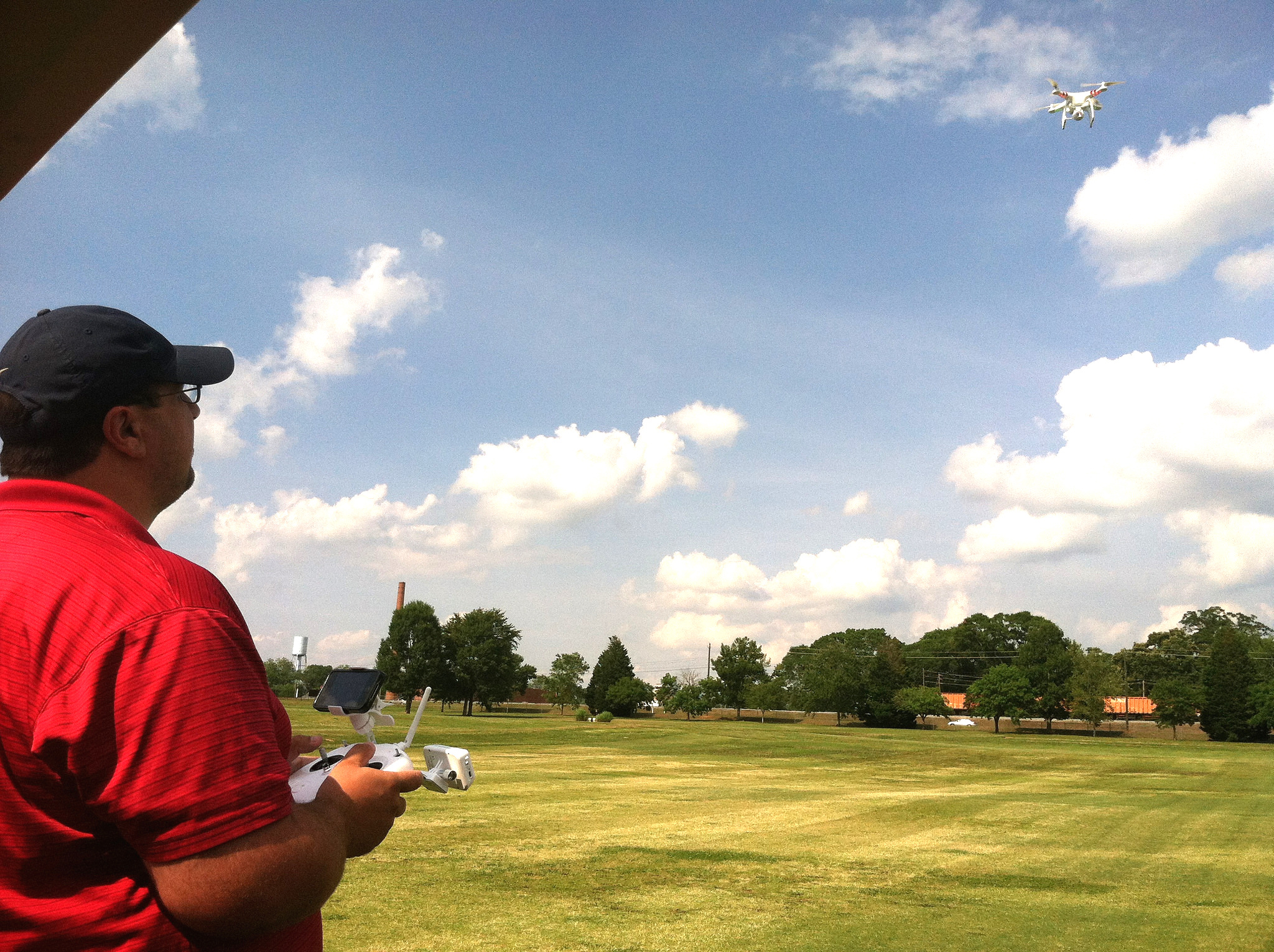 """University of Georgia research technician Clay Bennett """"pilots"""" an aerial drone over turfgrass research plots on the UGA campus in Griffin, Georgia. UGA Extension turfgrass specialist Clint Waltz uses the drone to reduce the amount of time he and Bennett spend documenting data in fields. They also use the drone to gather supplemental data through bird's-eye-view photographs of research plots."""