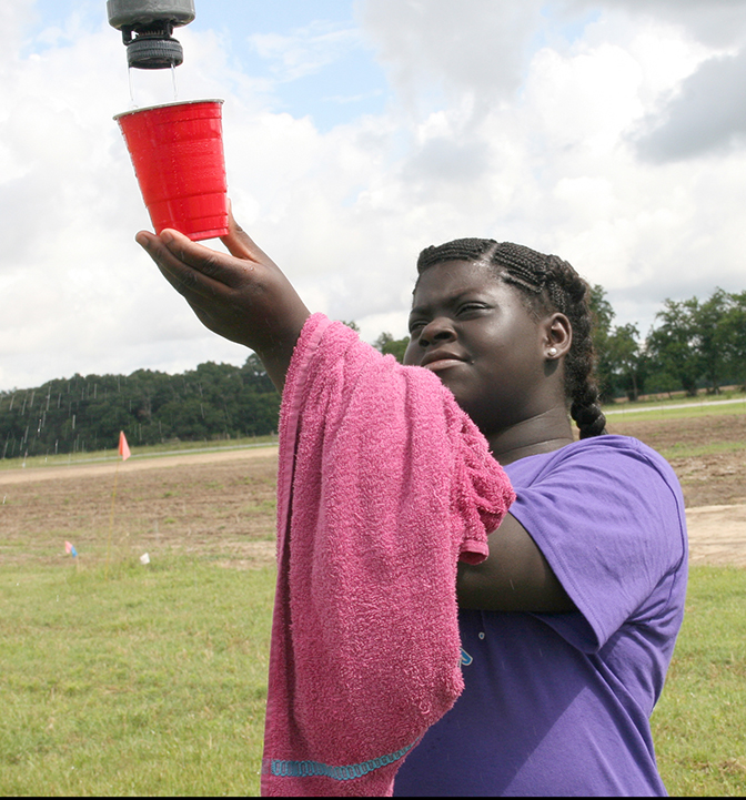Endue Brown, a Sumter County 4-H'er, collects water from an irrigation pivot during a previous 4-H20 camp.