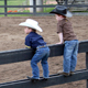 Two boys watch cowboys warm up before their events in the arena outside the Great Southland Stampede Rodeo in 2008.