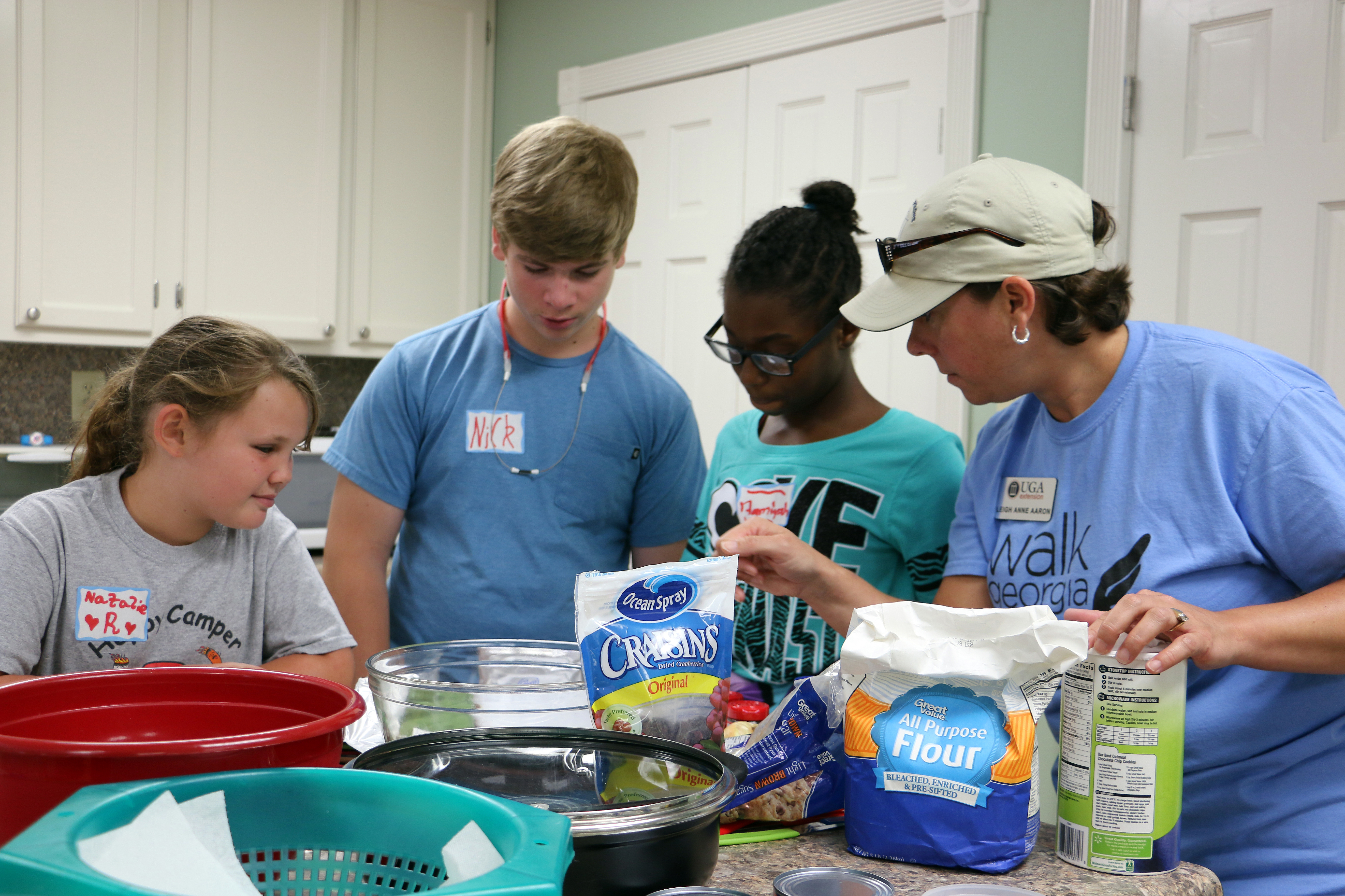 Morgan County 4-H'ers Natalie Ross, Nick Lewan and Aamiyah Jordan consult UGA Extension Family and Consumer Sciences Agent Leigh Anne Aaron about a recipe during the Morgan County Kids Can Cook camp held this summer.
