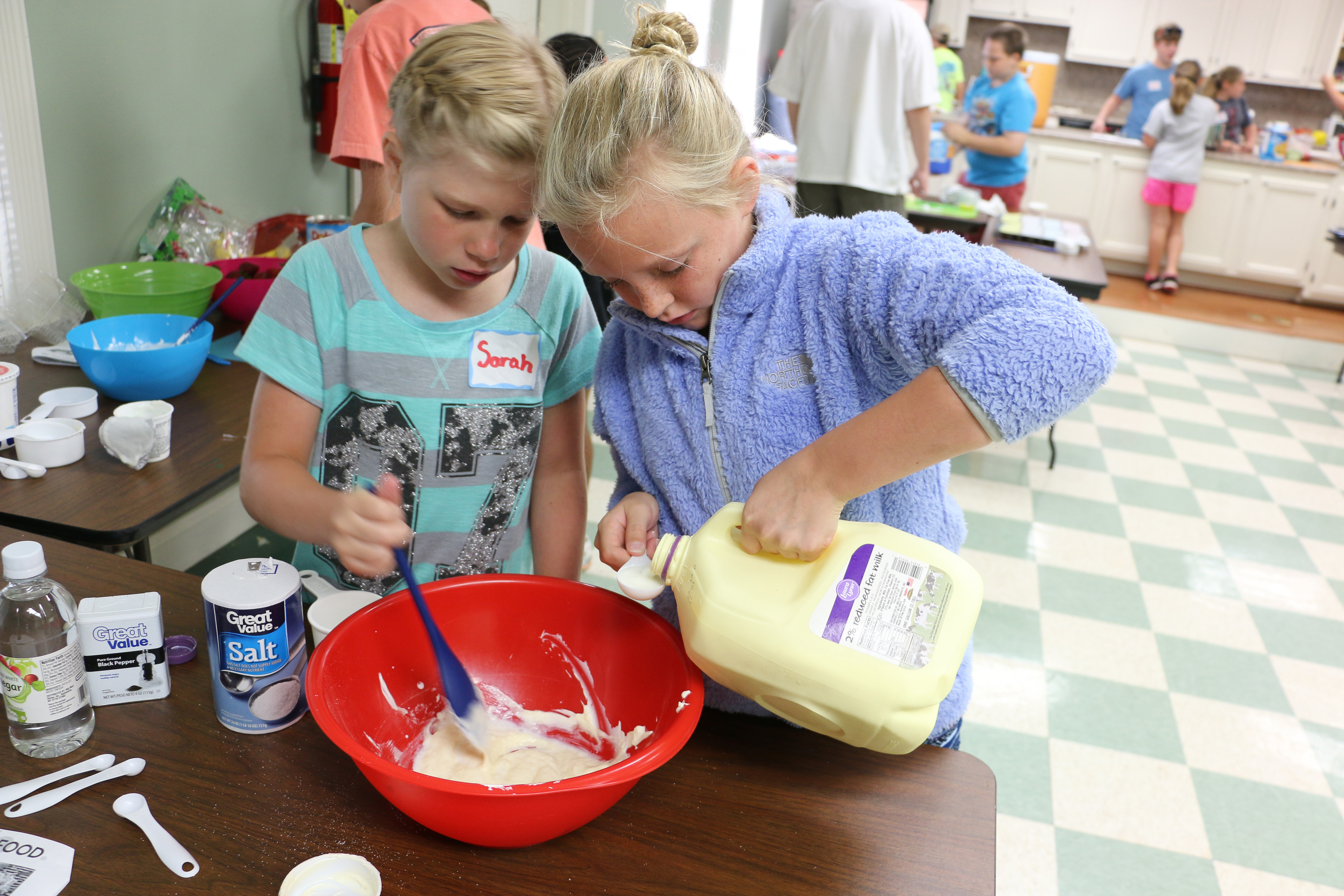 Sarah Bishop and Cailyn Berisko, Morgan County 4-H'ers, collaborate on a dressing for pasta salad during a Kids Can Cook camp this summer.