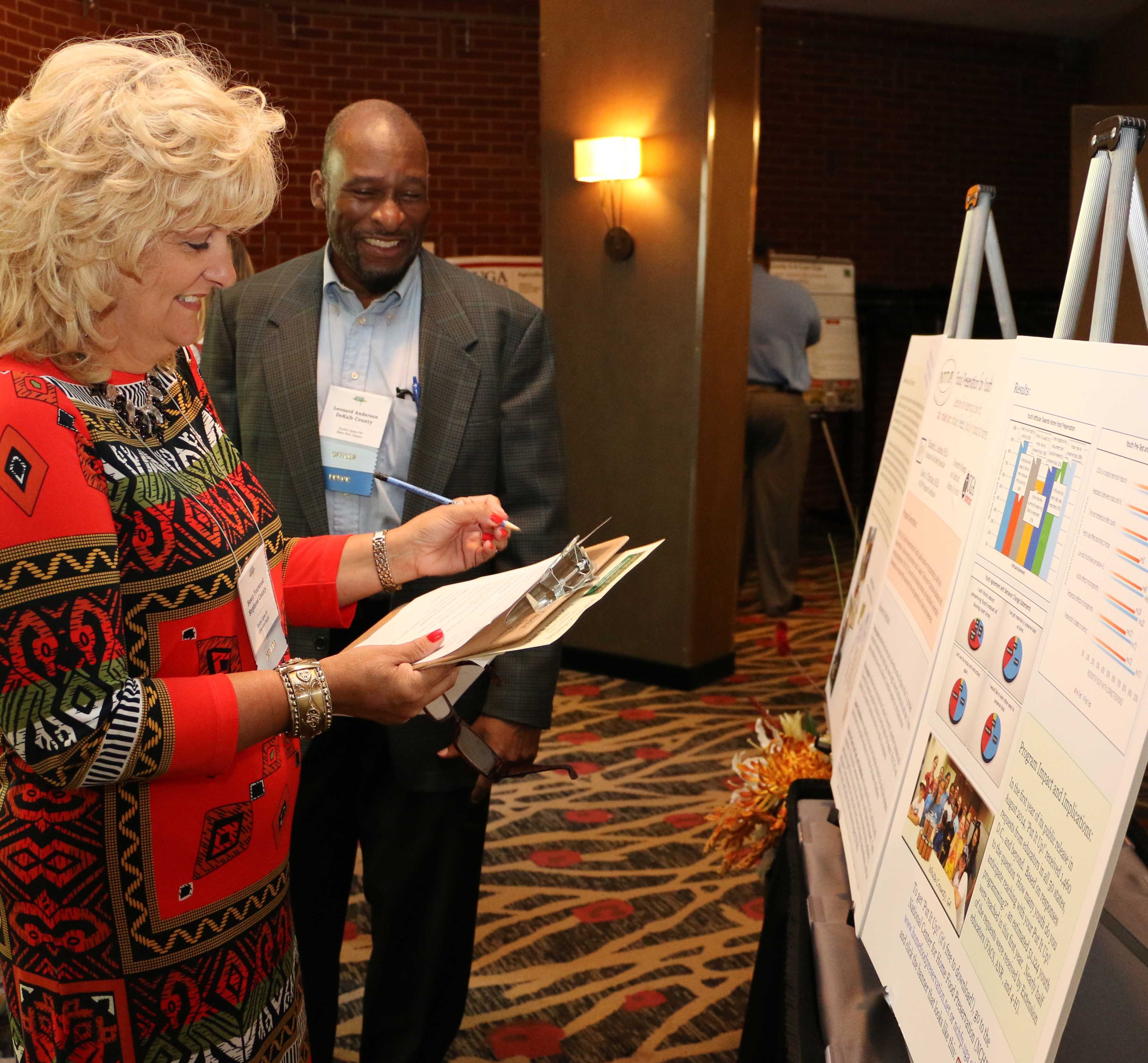Dekalb County Extension Agent Leonard Anderson and Stephens County Extension Agent Susan Yearwood judge a poster presentation during the 2015 Georgia meeting of Epsilon Sigma Phi. Epsilon Sigma Phi is a national professional organization for those working in the Cooperative Extension System.