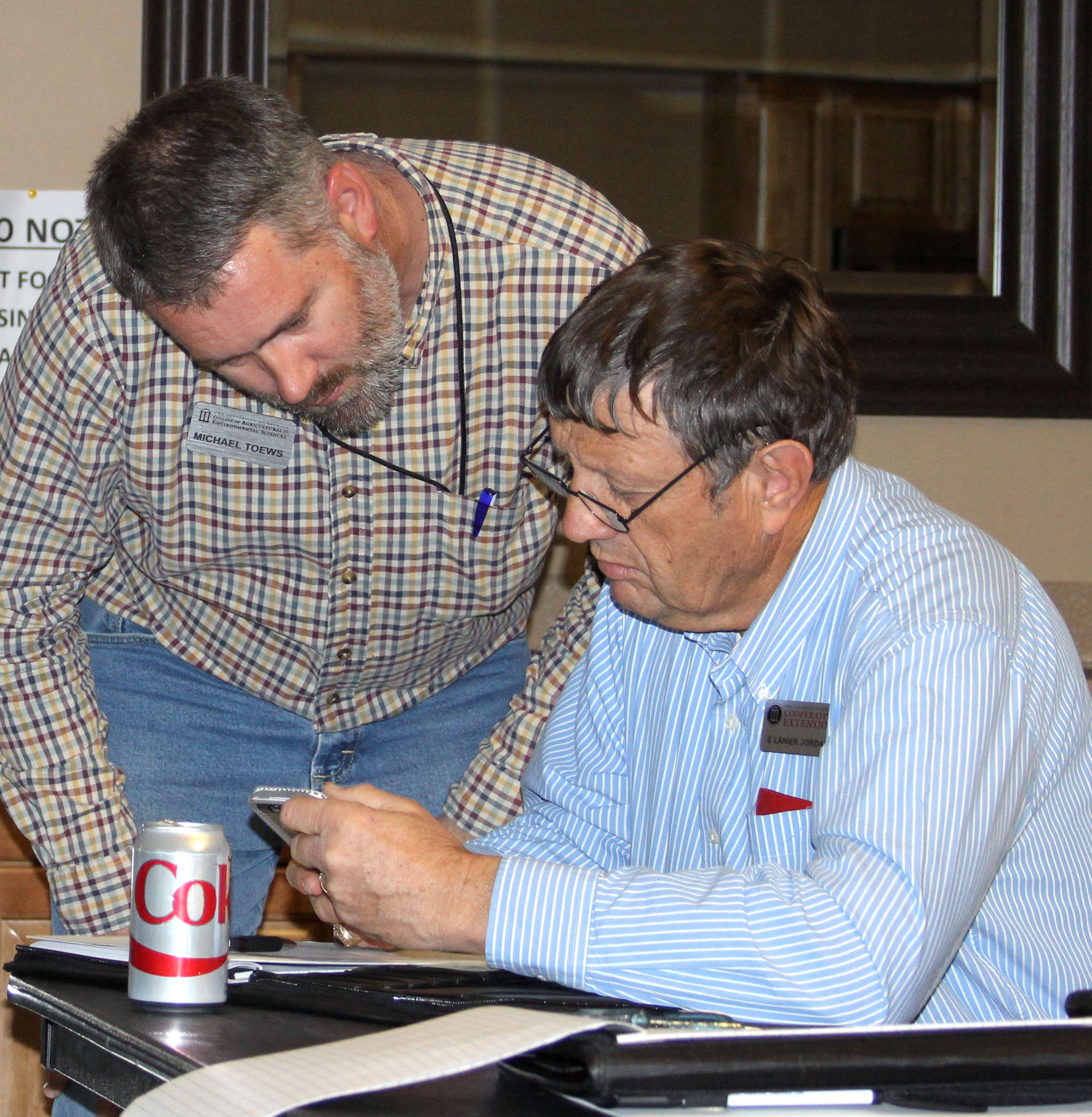 Farmers can get easy access to the latest research-based agriculture advice through a number of mobile apps available from the University of Georgia and other land-grant universities. UGA entomologist Michael Toews helps create these apps and holds workshops to share them with Georgia county agents and growers. Toews is shown (standing) sharing a mobile app with UGA Extension agent Lanier Jordan.