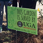 "Floyd County UGA Master Gardener Extension Volunteers stand with a ""This Garden is Served by UGA Cooperative Extension"" sign posted at community garden in Rome, Georgia."