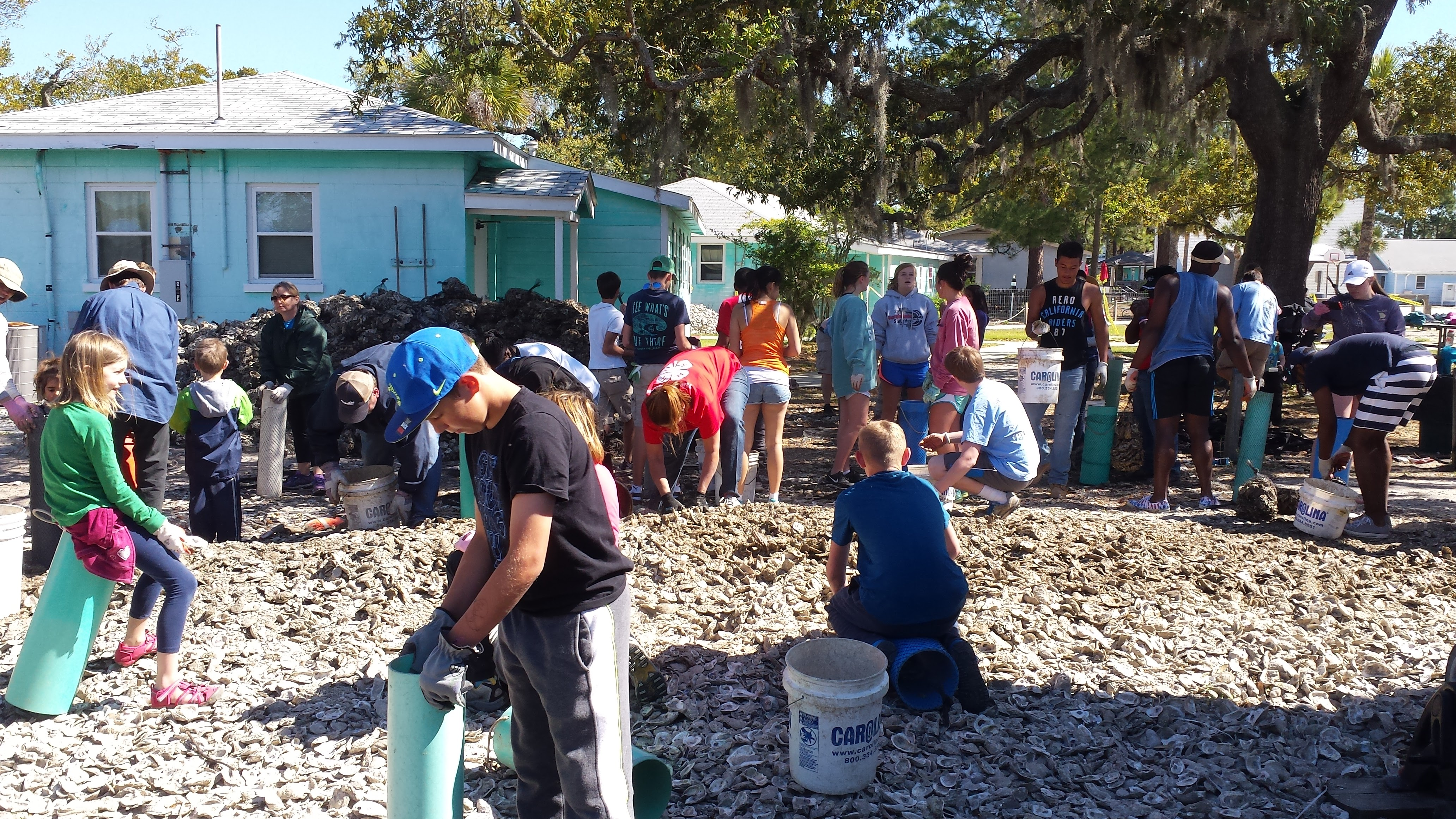 Volunteers fill Naltex bags with oyster shells at Burton 4-H Center on Tybee Island on April 9 to help build a living shoreline to prevent erosion at the environmental education center.