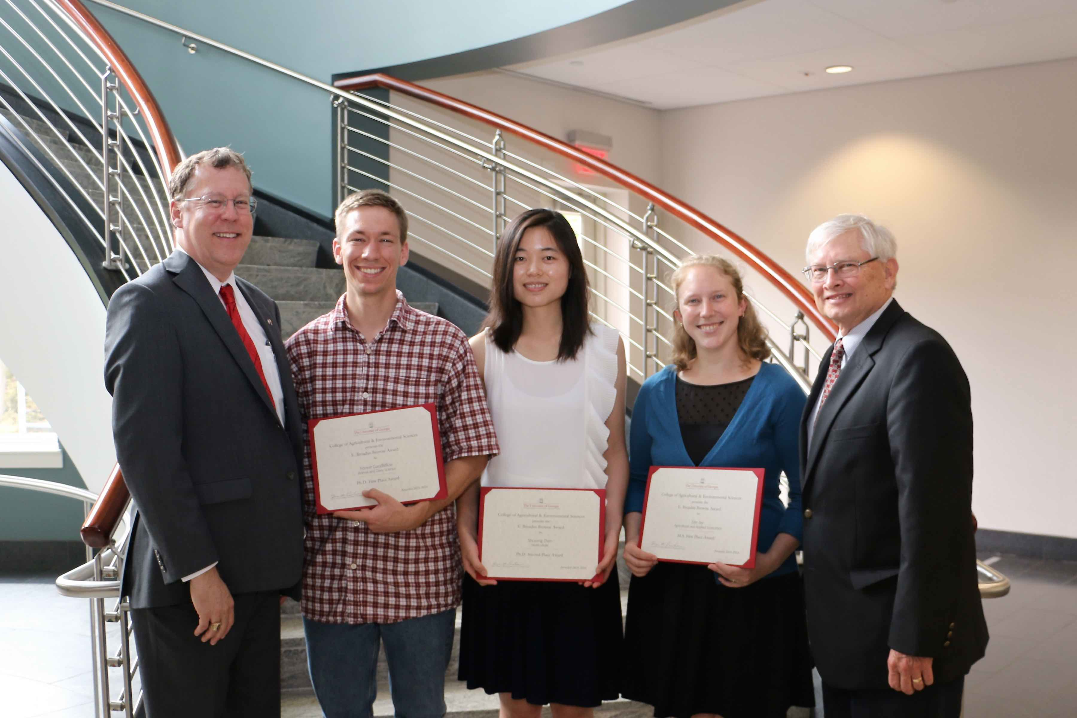 UGA College of Agricultural and Environmental Sciences Dean and Director Sam Pardue, far left, and CAES Associate Dean for Research Bob Shulstad, far right, congratulate doctorate students Forrest Goodfellow and Shuyang Zhen and master's degree student Erin Roestshcehl on their E. Broadus Browne Awards for creative research.
