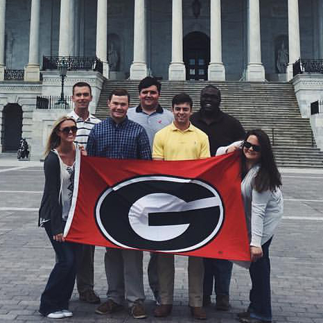 From left, CAES Congressional Agricultural Fellows Emily Smith, Brandon Poole, Guy Hancock, Jake Parker, Brock Pinson, Malik Grace and Brianna Roberts pose with a UGA flag in front of the U.S. Capitol.