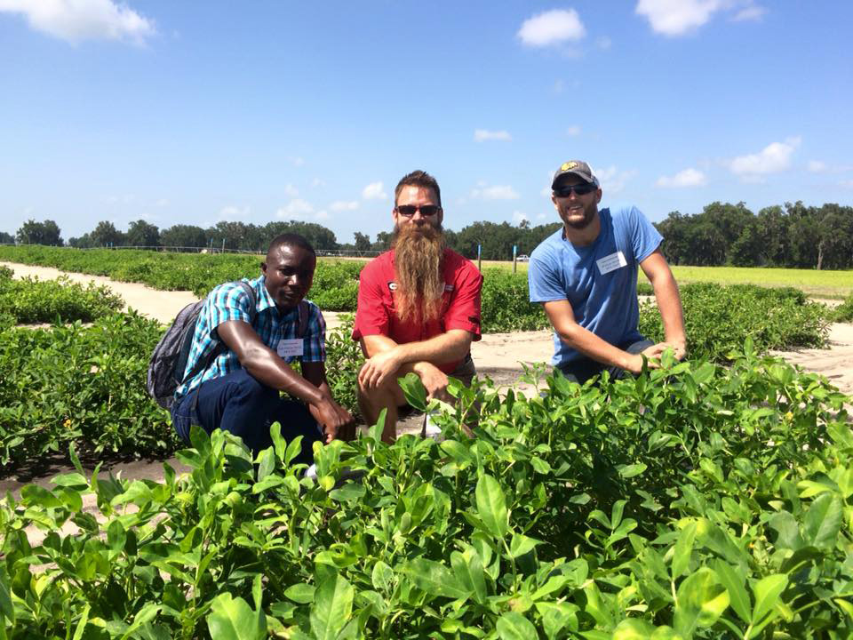 Abraham Fulmer (center) visits a U.S. peanut field with Haitian agronomist Jean Phillipe Dorzin (left) and Will Sheard of Meds & Food for Kids (right), in 2015.
