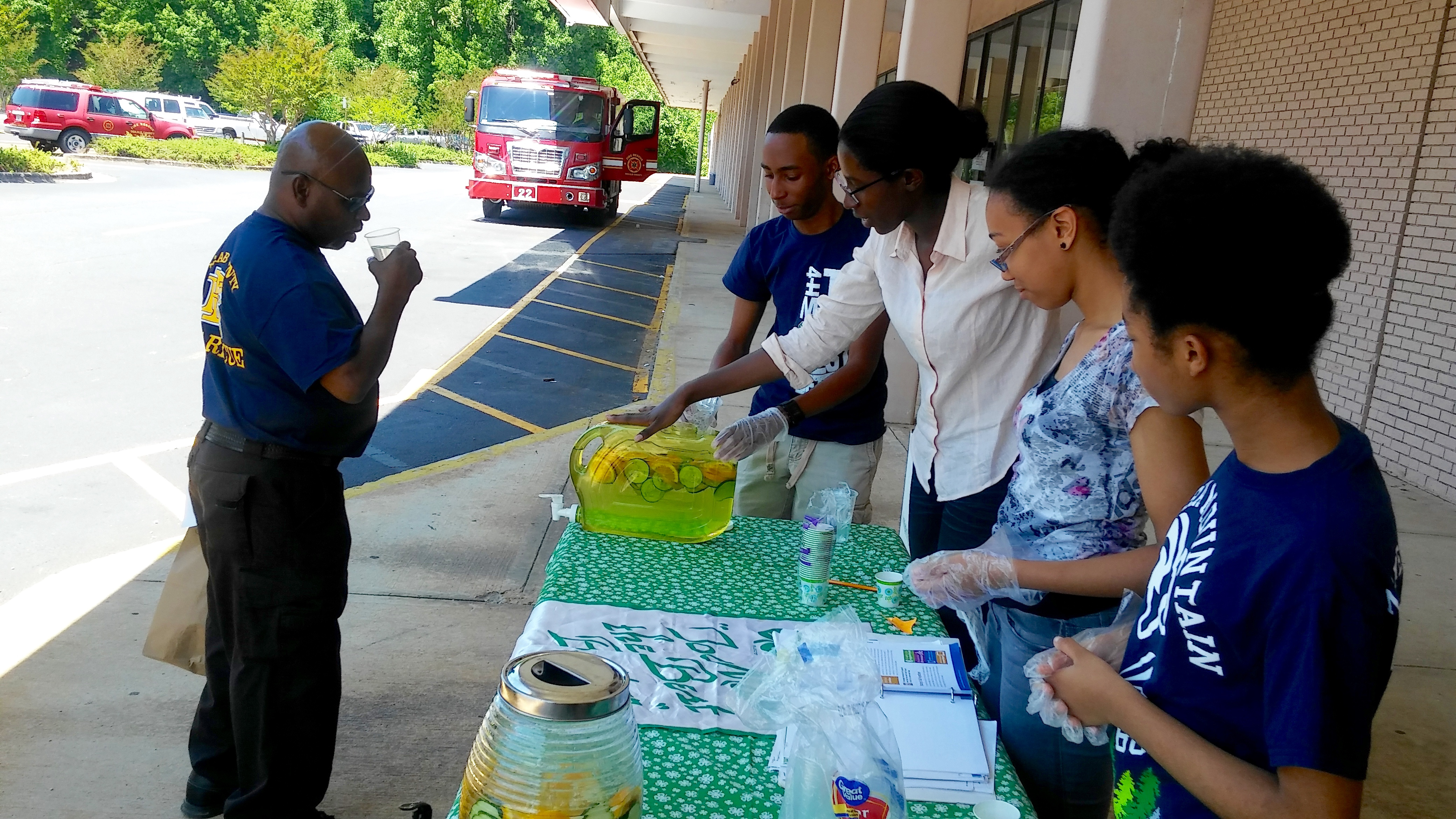 Decals County 4-H Club members Artis Trice, Nia Morrison, Chante' Lively and Claudia Thompson serve fruit infused water during the record-breaking first week of the DeKalb Mobile Market's 2016 season.