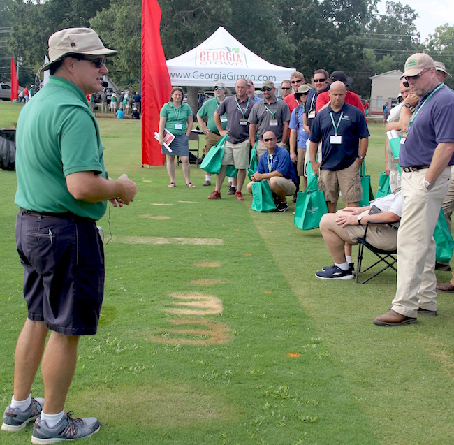 University of Georgia Cooperative Extension turfgrass specialist Clint Waltz was among the UGA experts who presented their research findings at the Turfgrass Research Field Day on Thursday, Aug. 4. Waltz is shown explaining how commonly used products, like insect repellant, sunscreen, cooking oil and powdered Gatorade, can harm a turfgrass lawn.