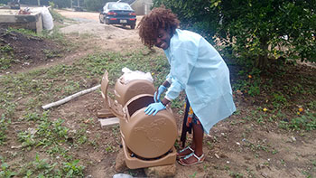 University of Georgia College of Agricultural and Environmental Sciences master's degree student Esther Akoto works with composting barrels as part of her research into whether composting kills the aflatoxin-producing molds in peanut field waste.
