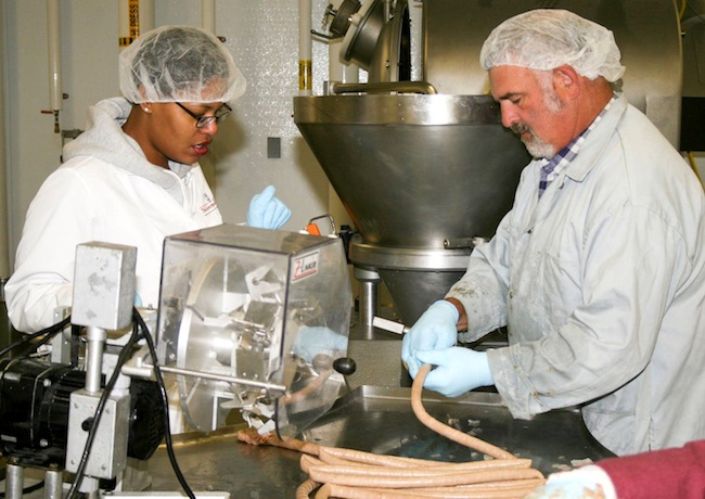 Carla Reed and Danny Morris stuff quail sausage links in a food science laboratory on the University of Georgia campus in Athens, Georgia.